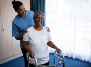 caregiver assisting the senior woman in her physical therapy