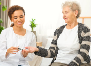 caregiver holding the hands of the senior woman