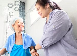 caregiver assiting the senior woman in bathroom
