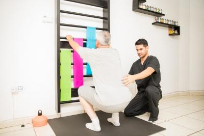 therapist helping a senior man exercise