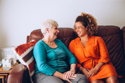 caregiver and her senior patient sitting on a couch