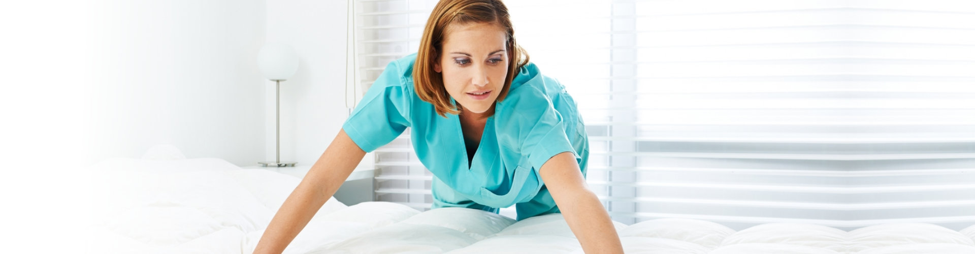 caregiver fixing the bed